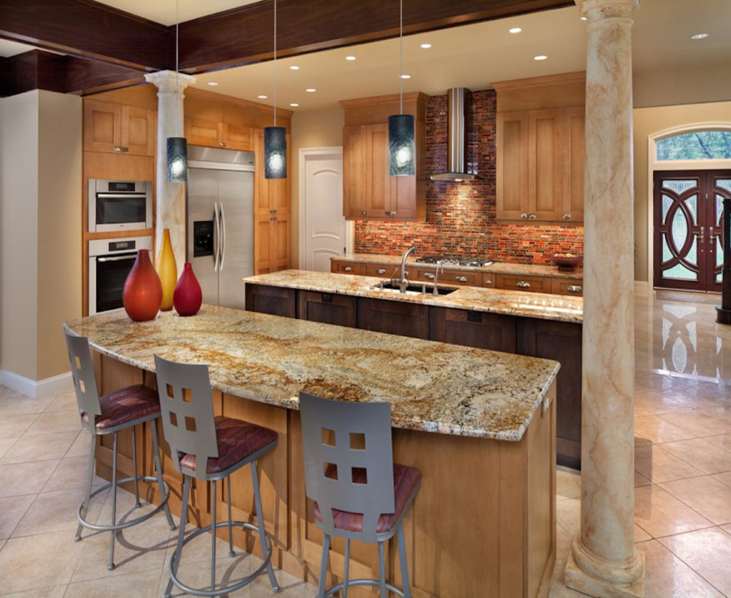 Warm tone double island kitchen with beige and gold granite, rust and brown backsplash, pendant lighting over seating island