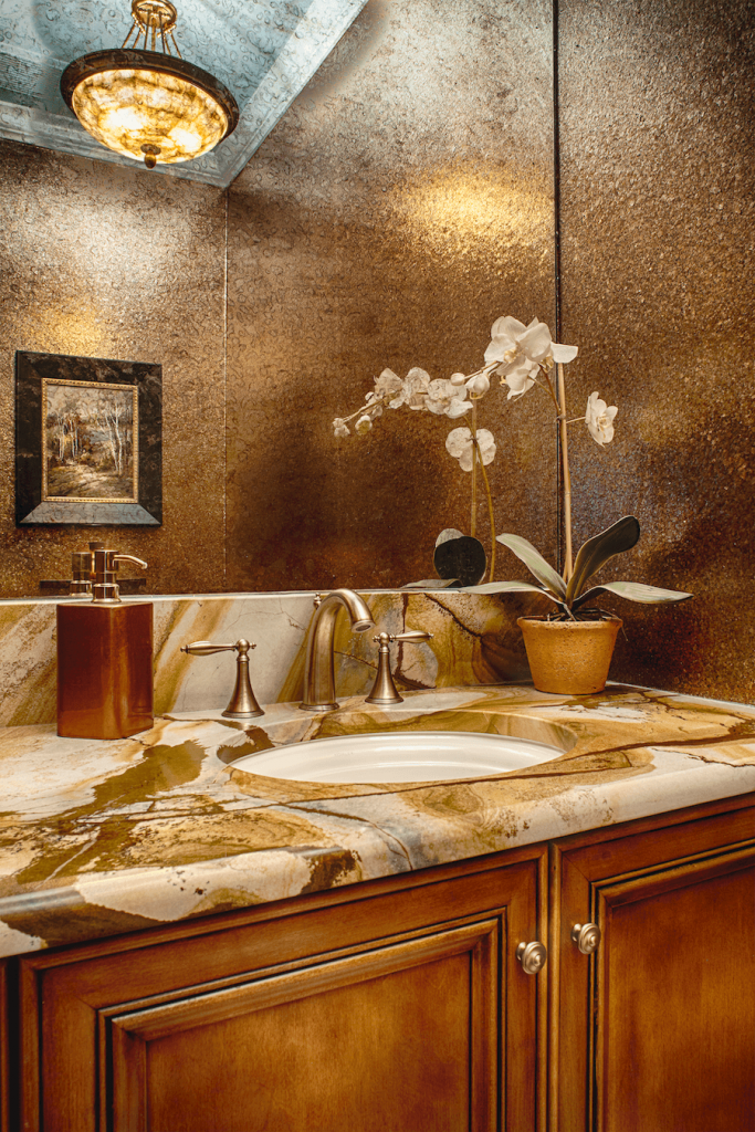 Powder room with crushed mica shell wallpaper walls and exotic marble counters