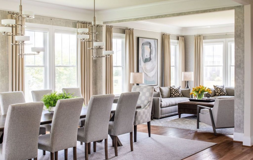 Contemporary dining room in soft grey chairs and rug, soft gold floor to ceiling window treatments, mottled soft toned wallpaper, contemporary chandelier