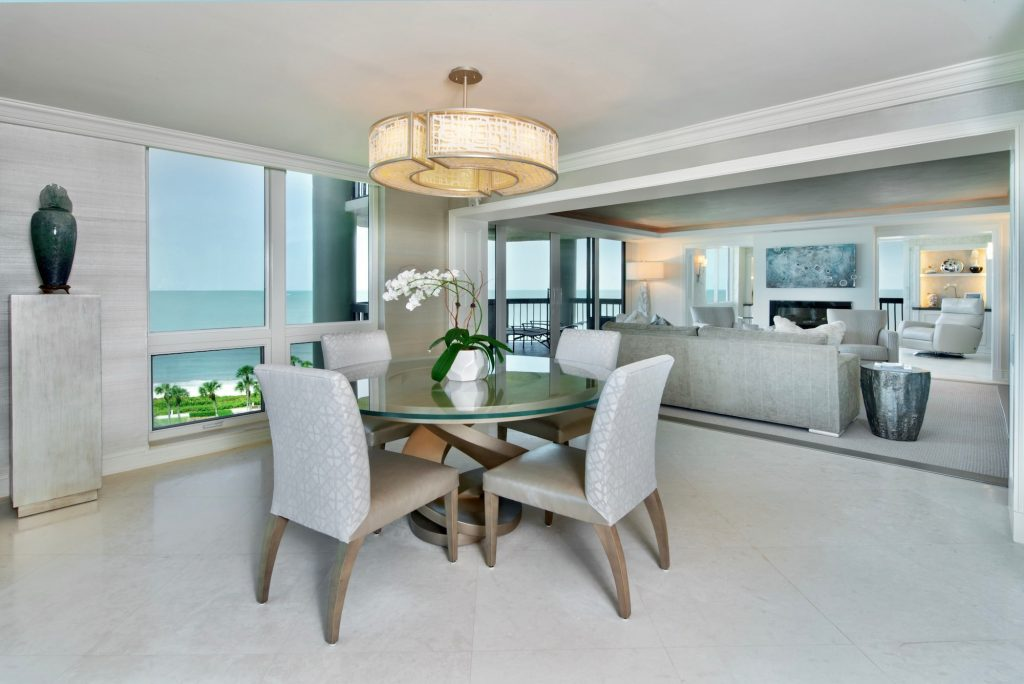 Contemporary Dining room for four with round glass table, round chandelier.