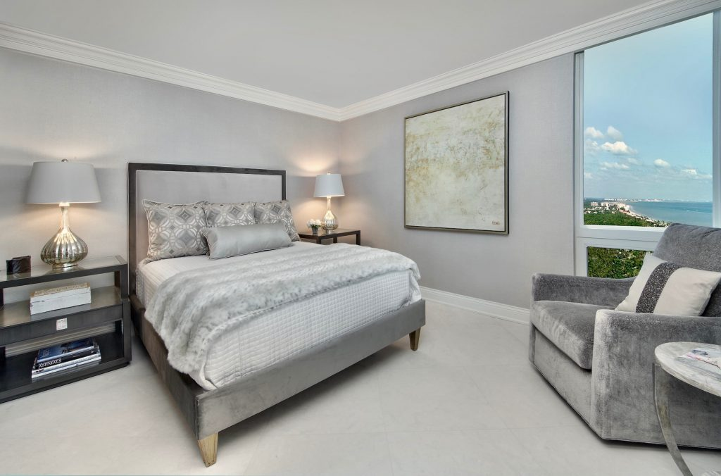Lovely guest bedroom with shades of grays with white and black accents. Contemporary art.