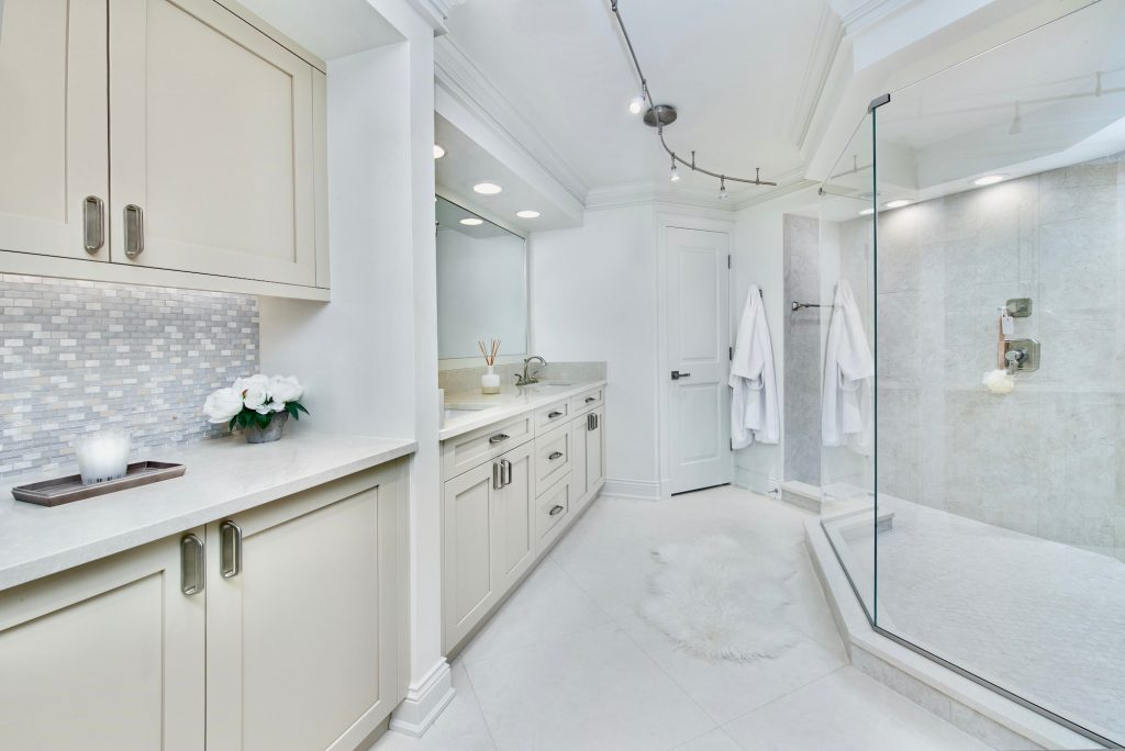 White and cream master bathroom with large glass shower and double sinks