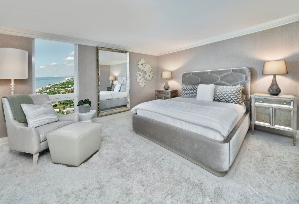 Rich contemporary master bedroom with shades of gray carpet, wall paper and fabric bedframe. Floor to ceiling mirror.