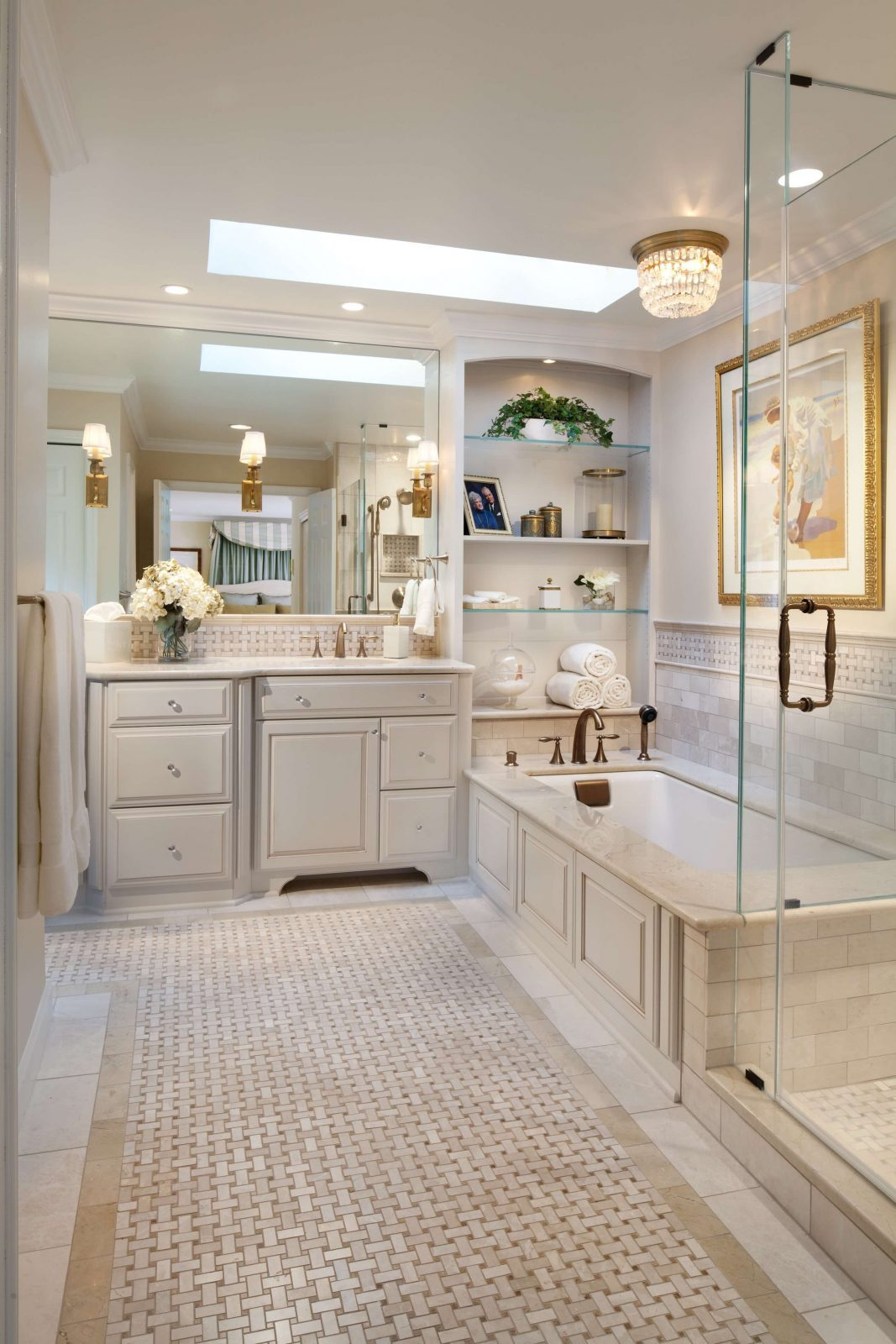 Master bathroom in shades of cream with built in shelves above the bathtub, glass shower, small crystal chandelier