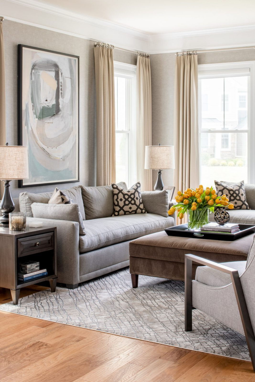 Contemporary living room in shades of grey and pale gold. Contemporary art and gold tulips