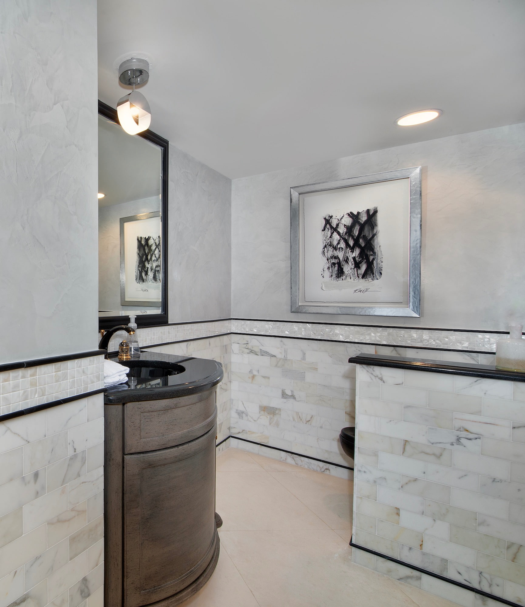 Elegant contemporary powder room with white marble walls and pale gray venetian plaster, black trim, sink and toilet